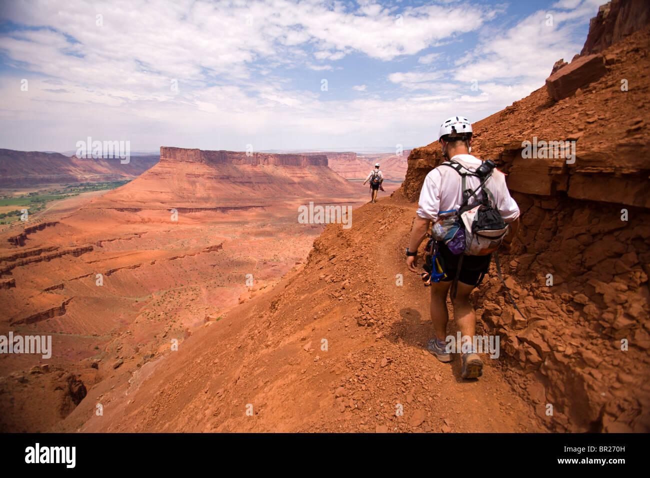 Abenteuer-Racer Wandern entlang einer Höhenloipe in einem Rennen in Moab, Utah (Silhouette). Stockbild
