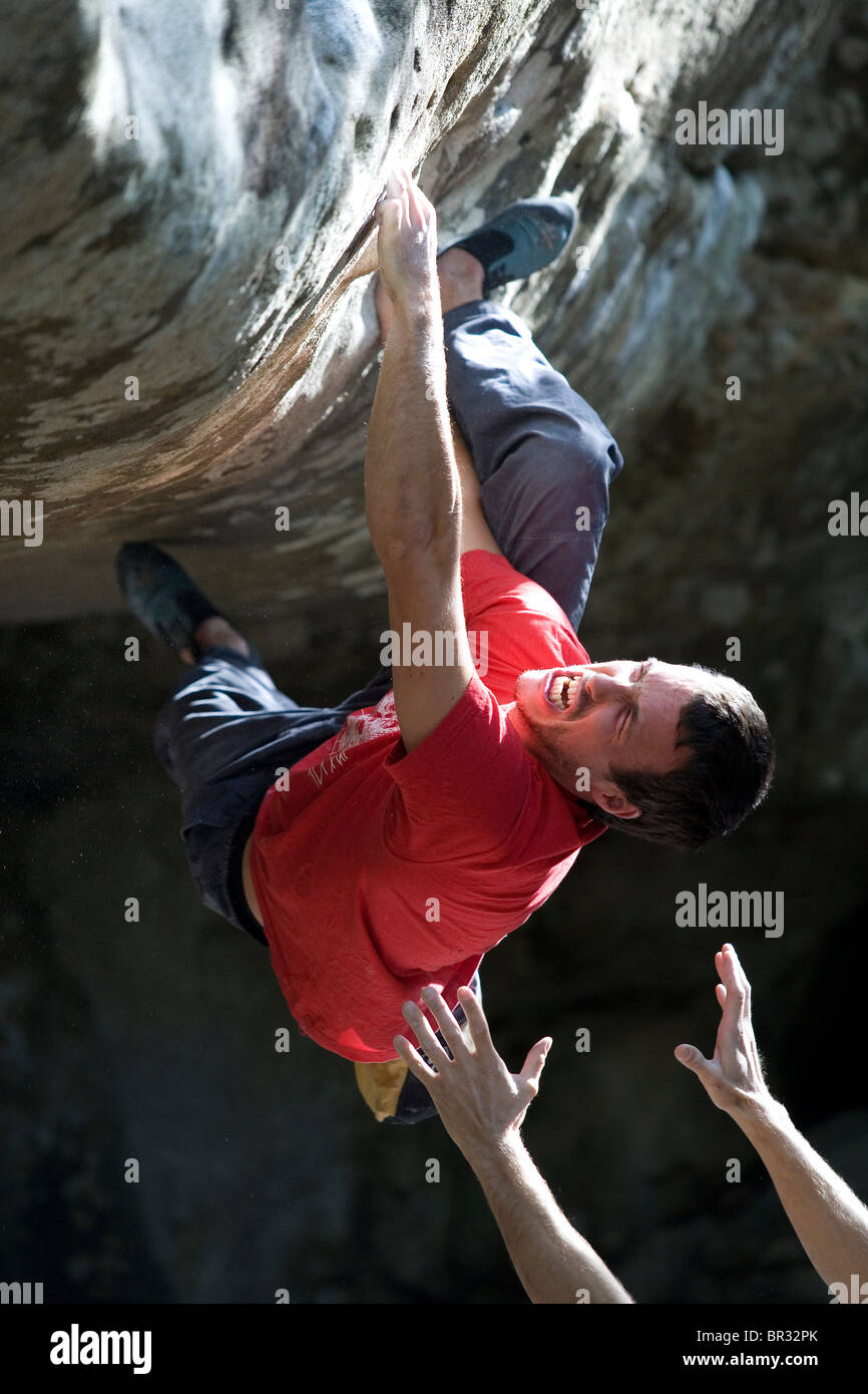Mann im roten Hemd hängt an seinen Fingern beim Klettern eines Sandstein-Überhangs. Stockbild