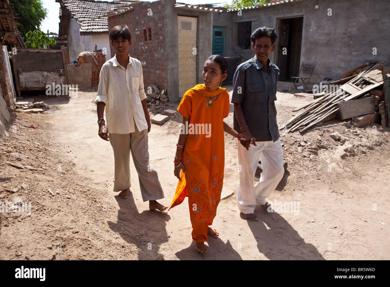 Hansa, die taub und blind ist durchschreitet ihr Dorf, begleitet von ihrem Vater und Bruder. Stockbild
