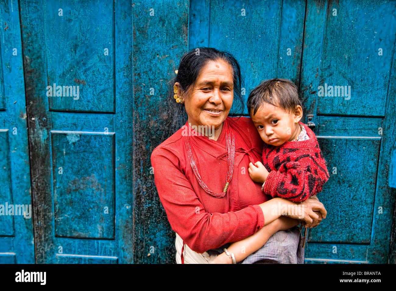 Frau mit großen Kind in Armen im Dorf von Bhaktapur eine Stadt in der Nähe von Kathmandu Nepal lokale Stockfoto