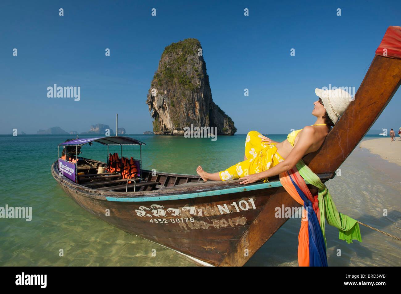 Frau, entspannend auf einem Longtail-Boot am Laem Phra Nang Beach, Krabi, Thailand Stockbild