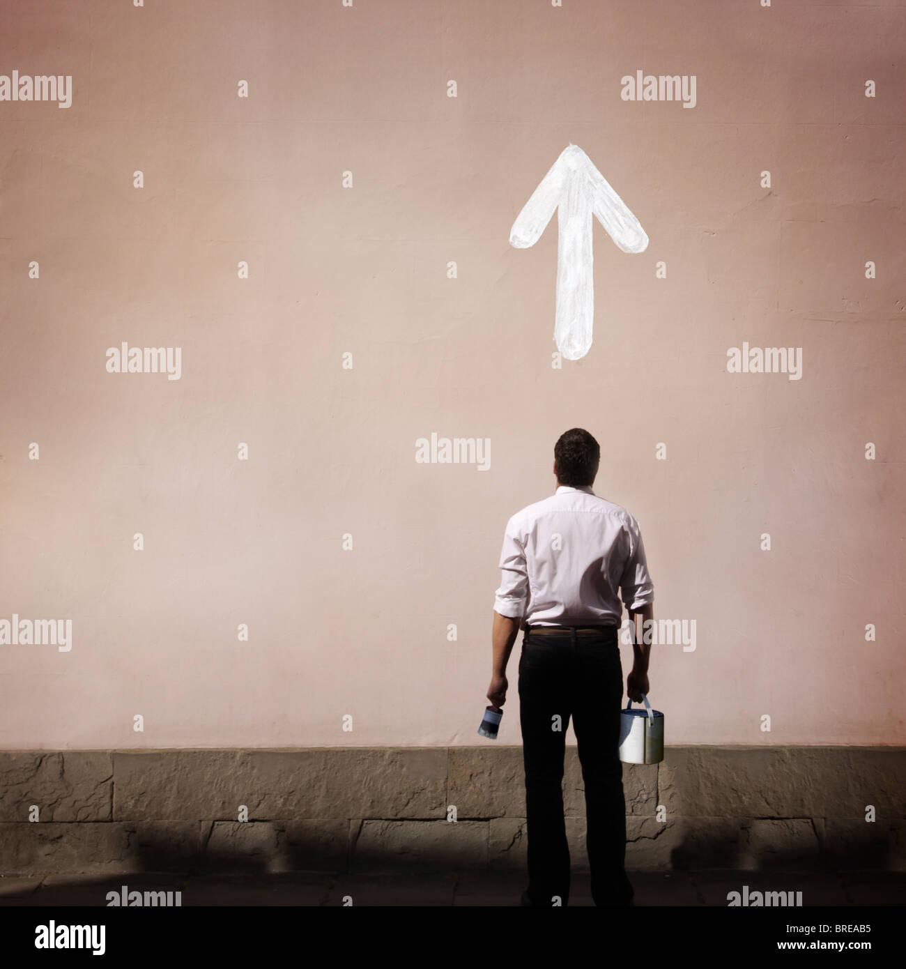 Mann mit Pfeil an die Wand gemalt Stockbild
