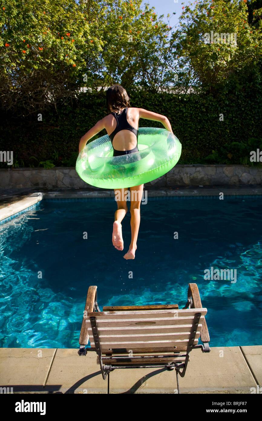 Mädchen mit Innenrohr Sprung ins Schwimmbad Stockbild