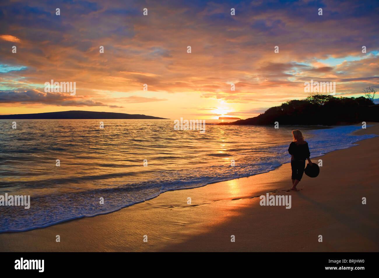 schöne Mittelalter Frau zu Fuß am Ufer allein auf Makena Beach, Maui bei Sonnenuntergang Stockbild