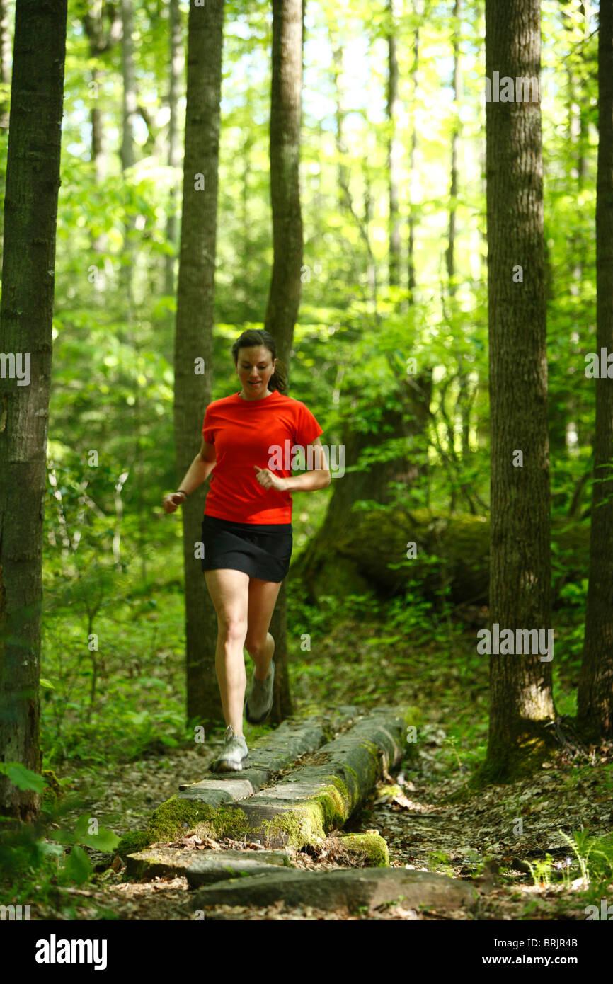 Trailrunning-Frau in einem üppig grünen Wald. Stockbild
