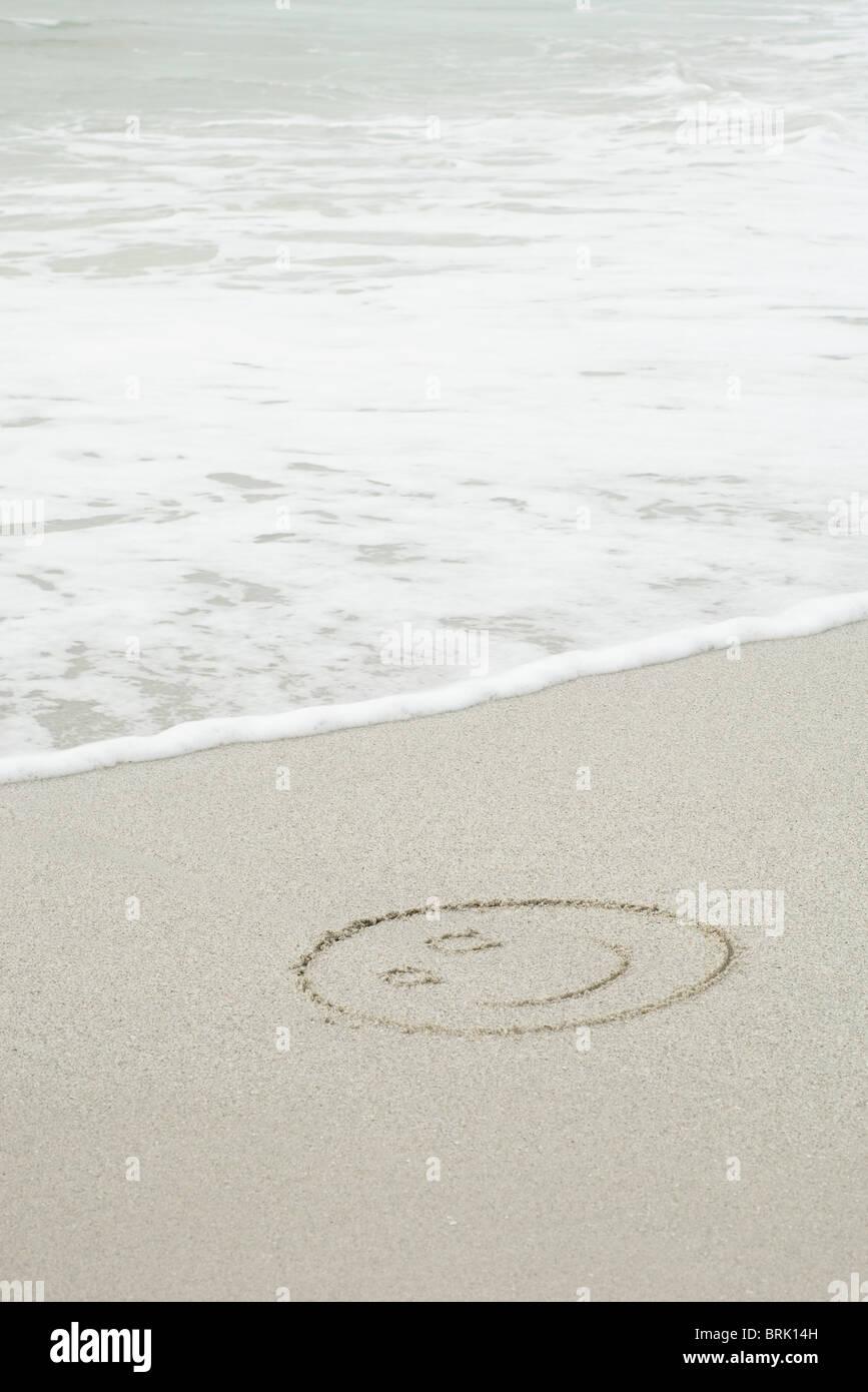 Smiley-Gesicht gezeichnet im Sand am Strand Stockbild