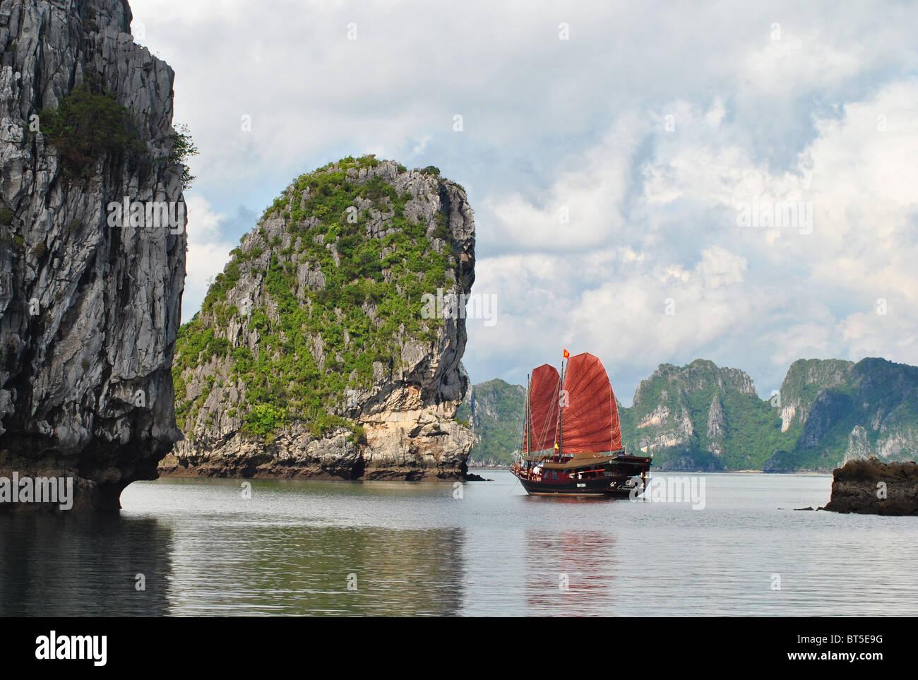 Dschunke mit roten Segel unter Kalksteininseln in Ha Long Bucht, Vietnam Stockbild