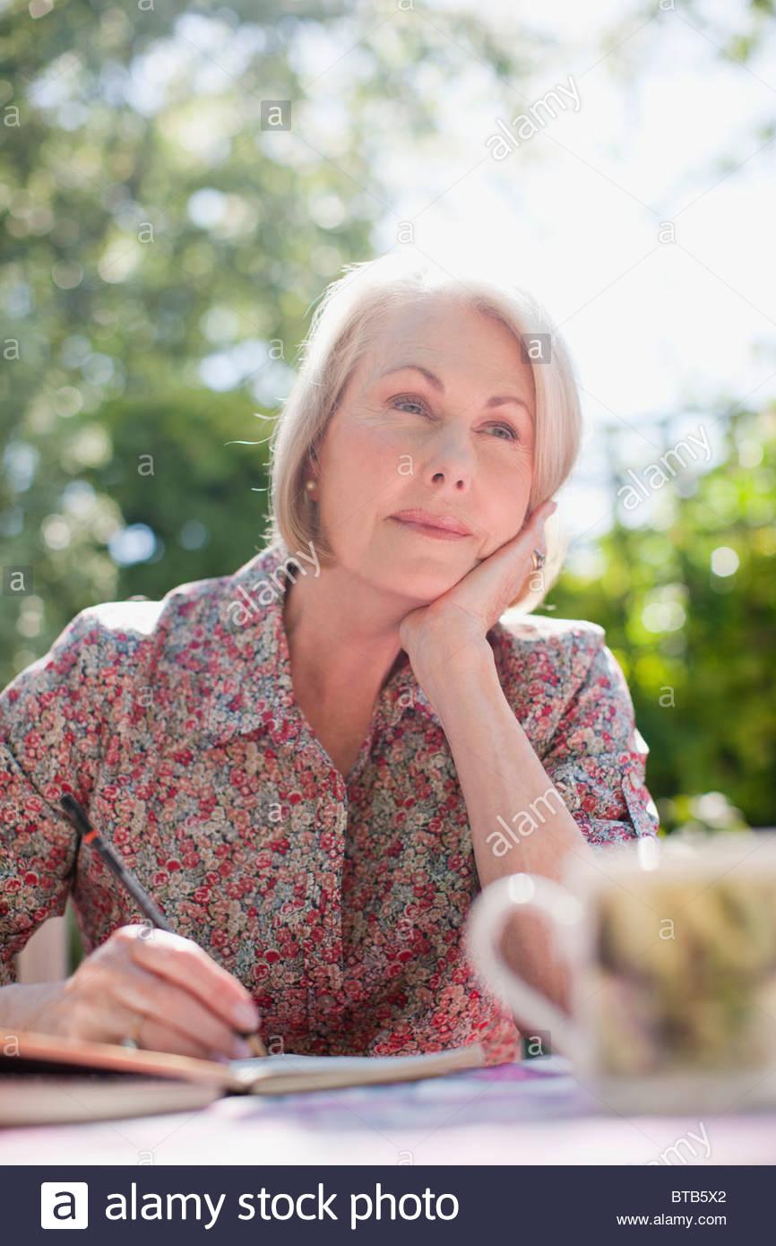 Nachdenkliche Frau in Fachzeitschrift an Terrassentisch Stockfoto