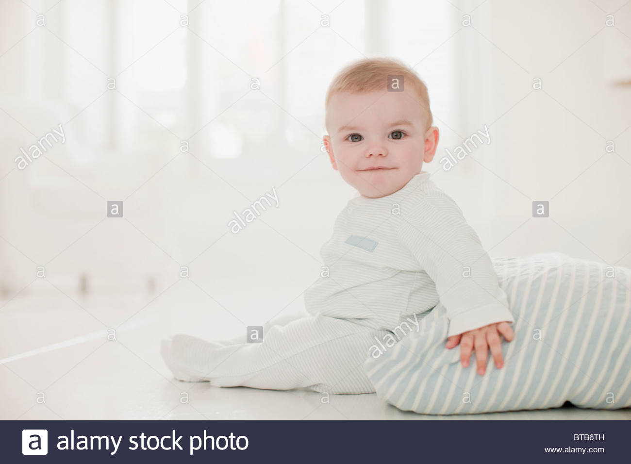 Lächelnden Baby Erdgeschoss mit Kissen Stockbild