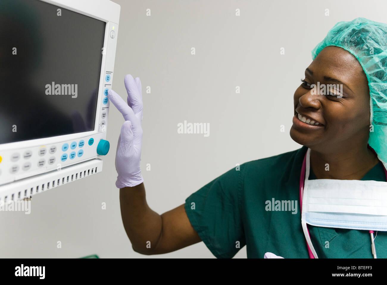 Ändern der Einstellungen auf medizinische Geräte Monitor Mitarbeiter Stockbild