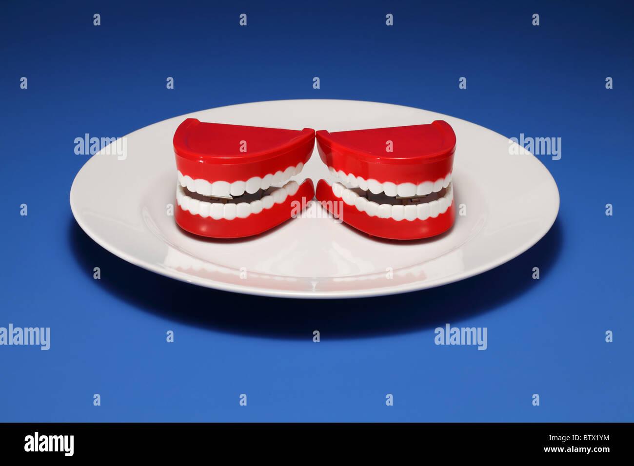 Zwei plastische Zahnfleisch und Zähne auf einem weißen Teller Stockbild