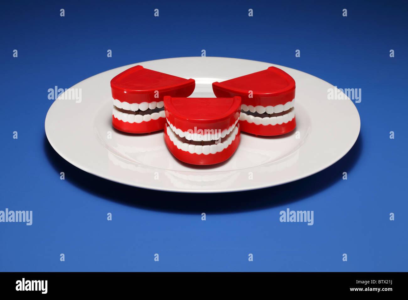 Drei plastische Zahnfleisch und Zähne auf einem weißen Teller Stockbild