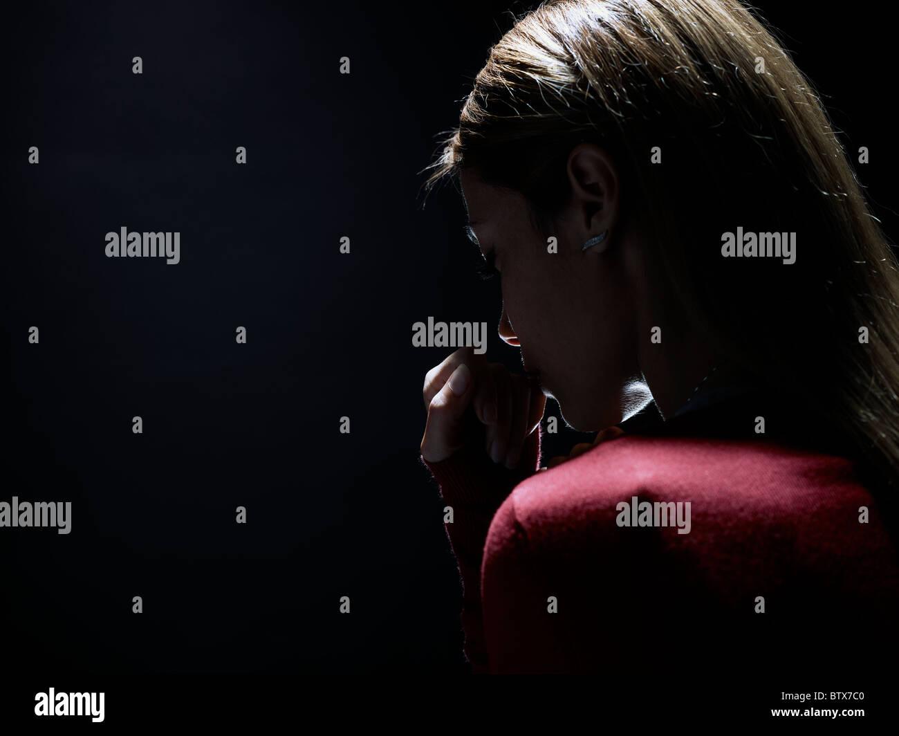 nachdenkliche Frau auf schwarzem Hintergrund, stellvertretend für das Konzept der Anonymität Stockbild