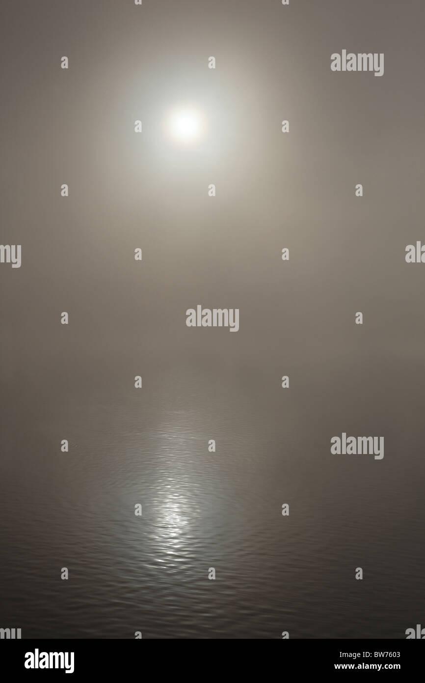 Die Sonne an einem nebligen See reflektiert Stockbild
