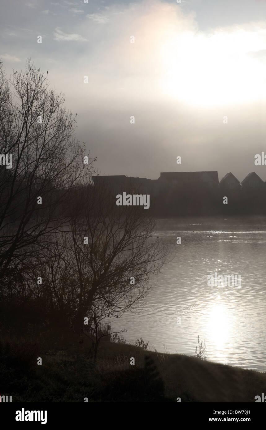 Ein nebeliger Morgen an einem See mit Häusern in der Ferne, die Sonne auf dem Wasser schimmern. Stockbild