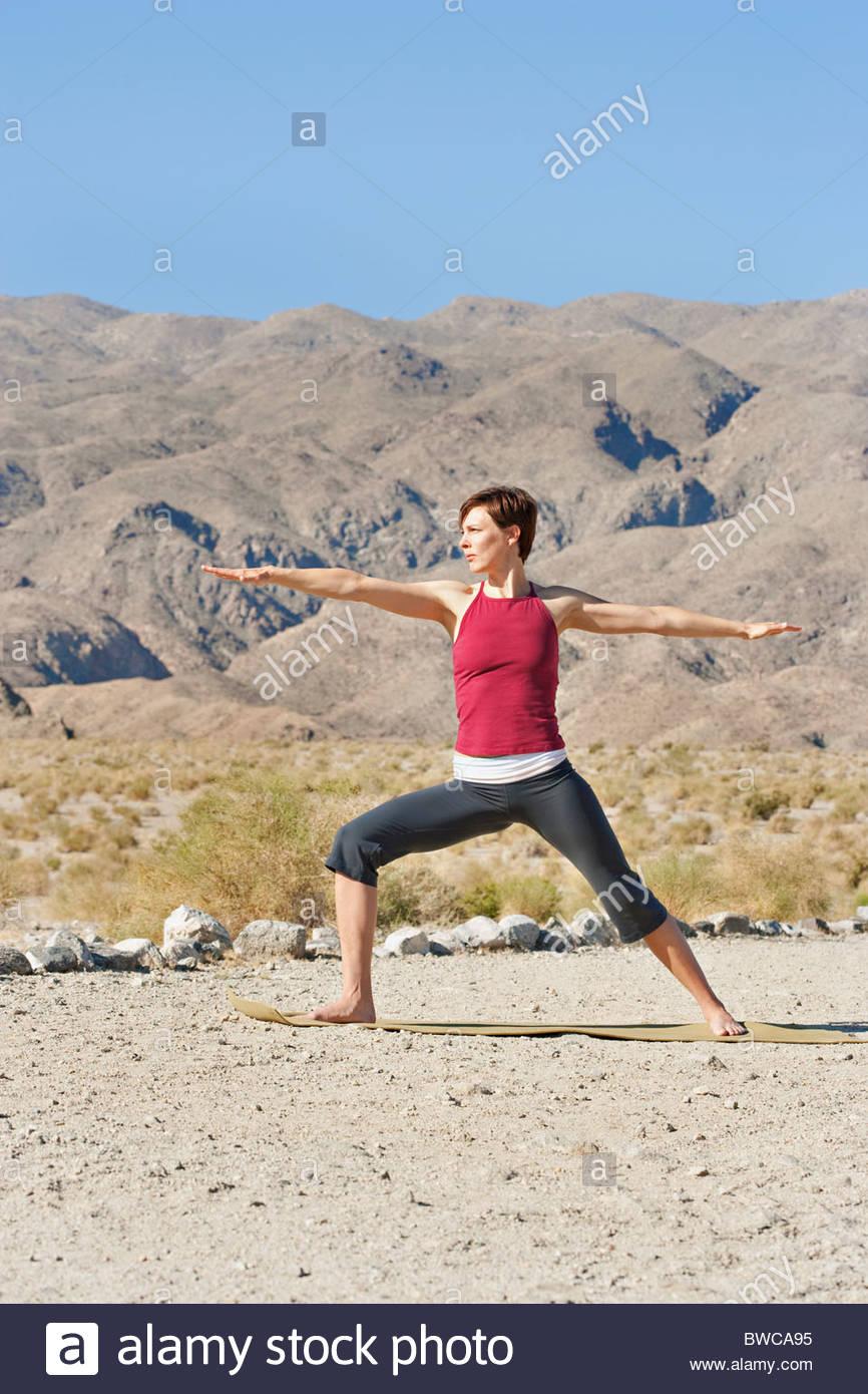 USA, Kalifornien, La Quinta, Frau stehend in Yoga-Krieger-Pose in Wüstenlandschaft Stockbild