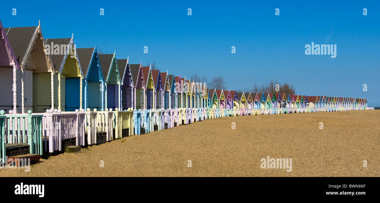 Pastell Strandhütten erstrecken sich über einen Strand in einem Bogen Stockbild