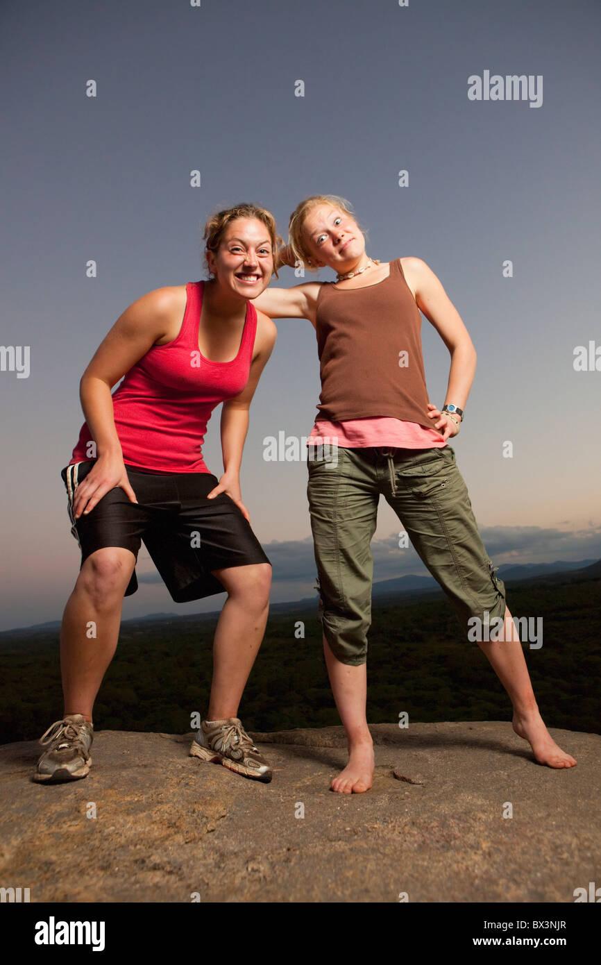 Zwei junge Frauen tun alberne Posen auf einem Felsen; Manica, Mosambik, Afrika Stockbild