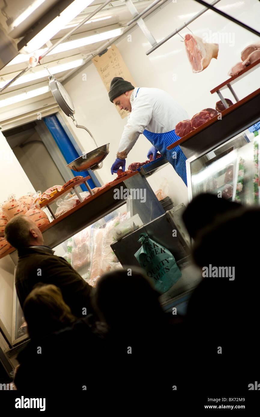 Ein Standbesitzer verkaufen billige Fleischstücke an marktgerechten November Aberystwyth, Wales UK Stockbild