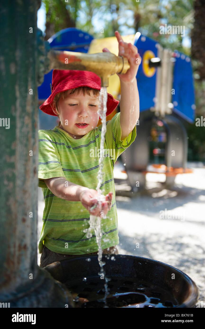 Kleiner Junge waschen seine Hand in Wasserbrunnen außerhalb auf Spielplatz Stockbild