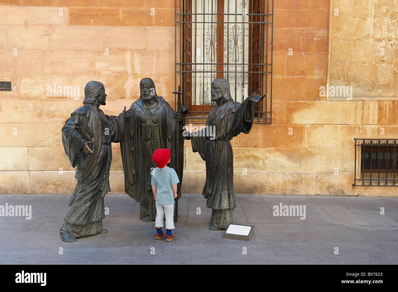 Kleiner Junge Blick auf religiöse Statuen in historischen Platz Stockbild