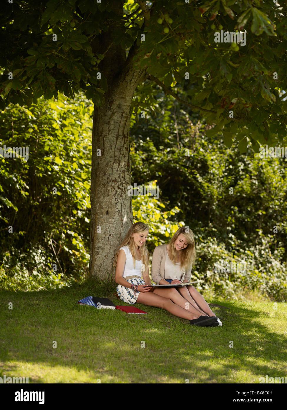 Zwei Mädchen, die unter einem Baum zu arbeiten Stockbild