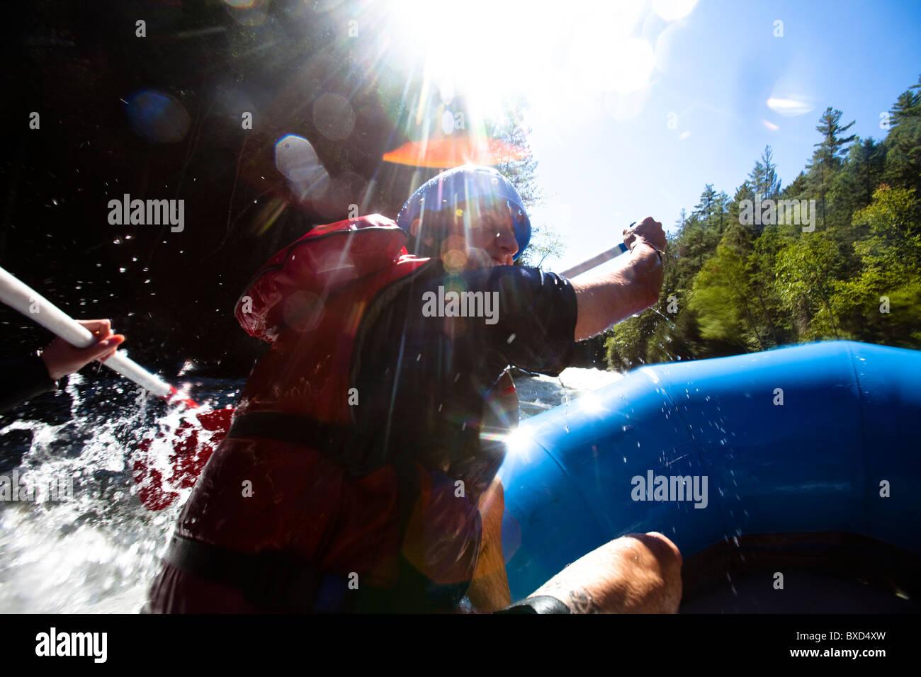 Ein junger Mann paddelt beim Wildwasser-rafting einen Fluss hinunter. Stockbild