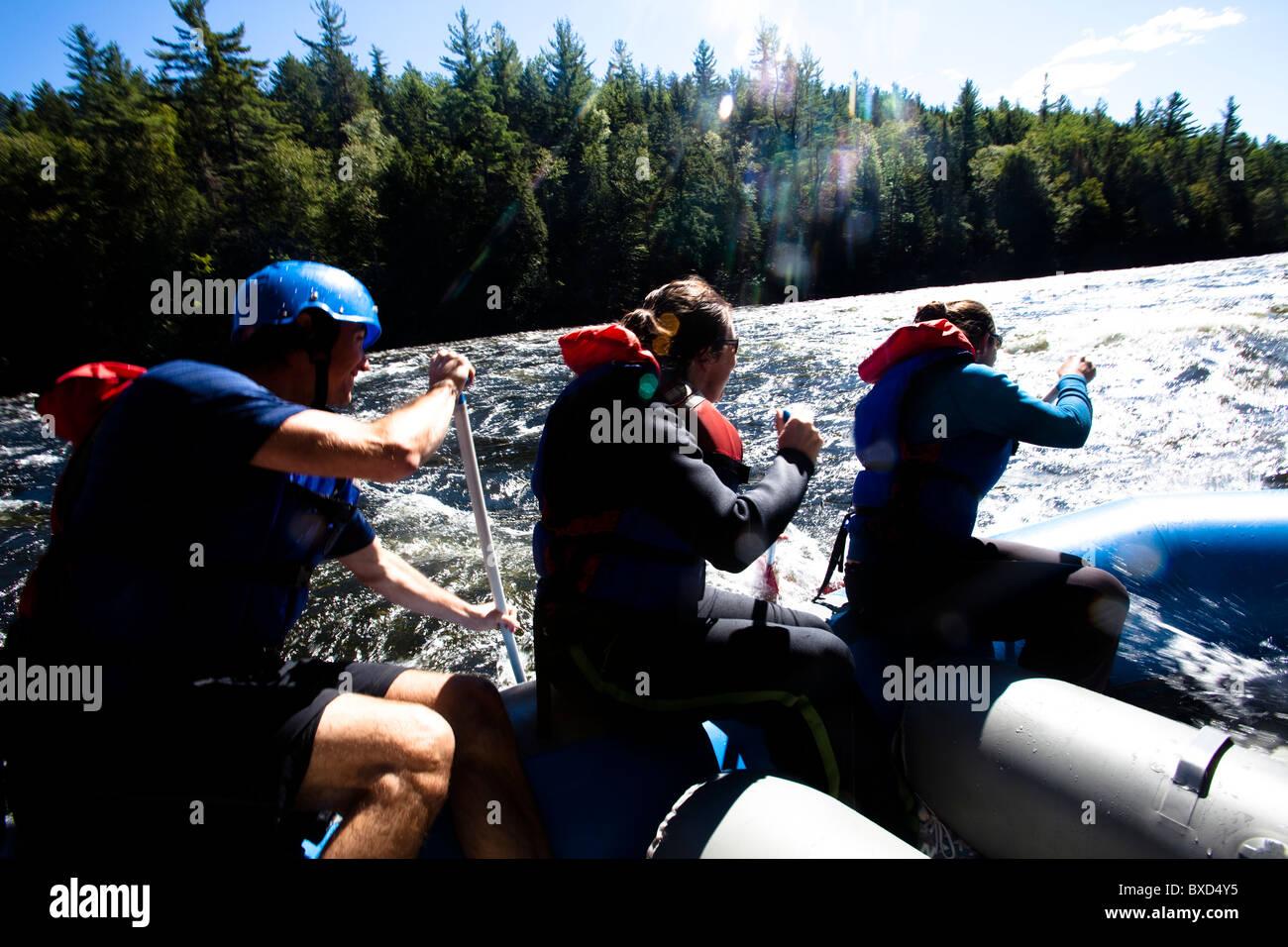Eine Gruppe von Erwachsenen Wildwasser-rafting in Maine. Stockbild