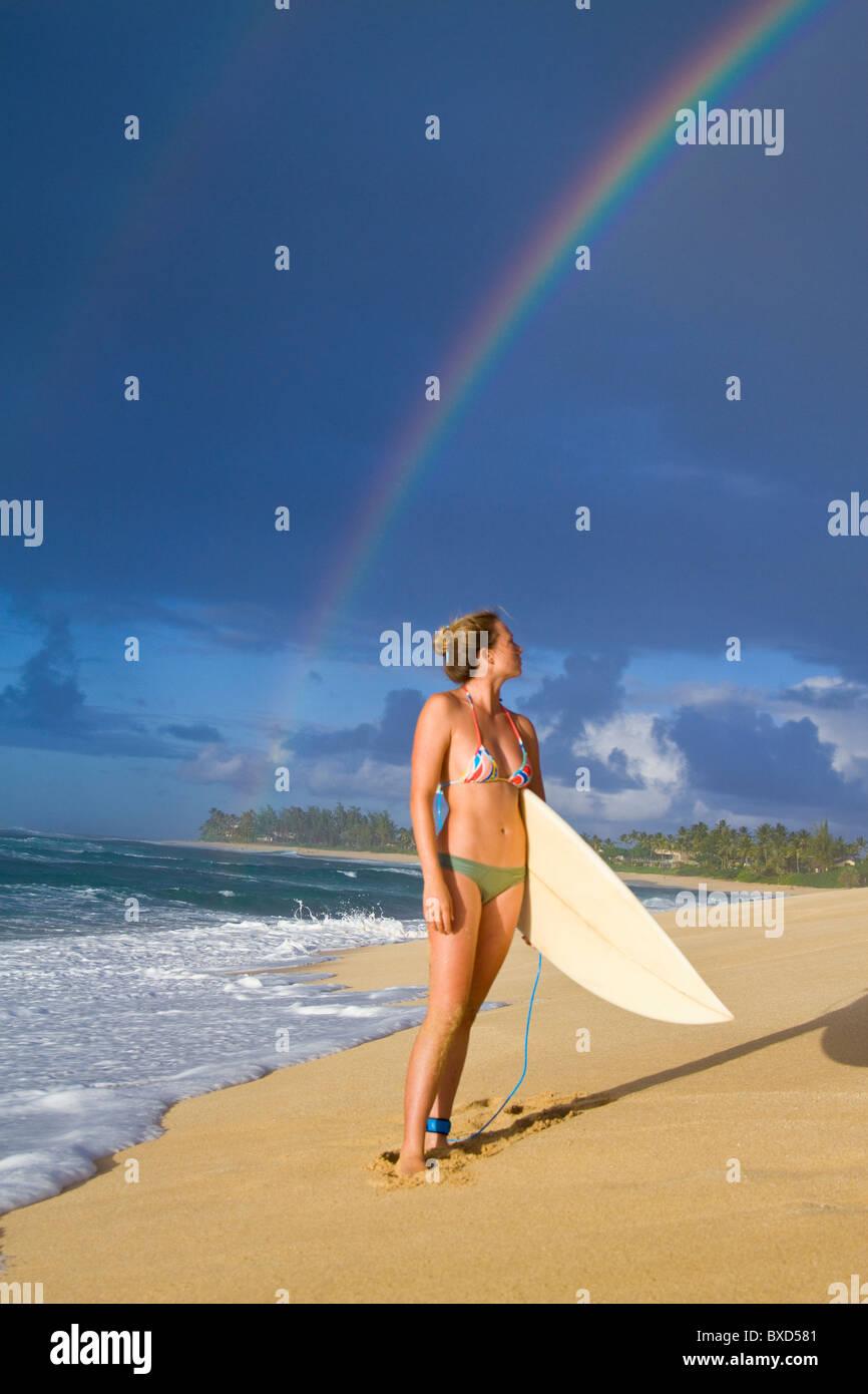 Eine erstaunliche Regenbogen über Rocky Point, als Surfer Mädchen Spaziergänge am Strand, auf der Stockbild