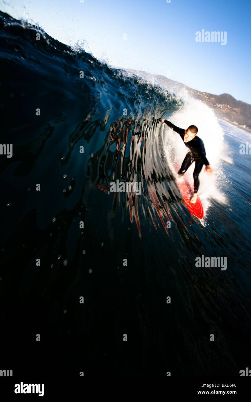 Eine männliche Surfer zieht in ein Fass im Zuma Beach in Malibu, Kalifornien. Stockbild