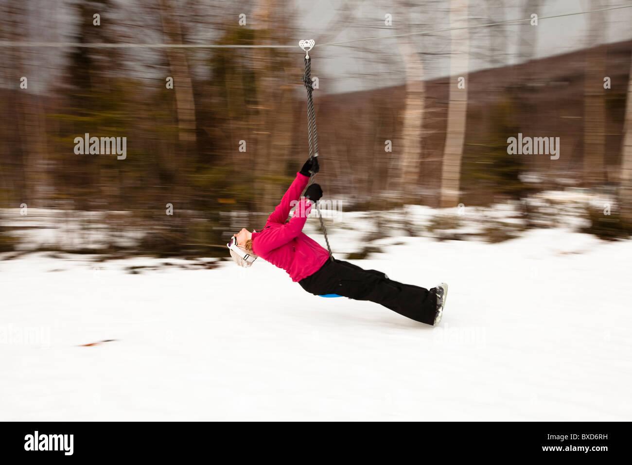 Eine Frau spielt auf eine Seilrutsche in Bretton Woods, New Hampshire. Bewegungsunschärfe. Stockbild