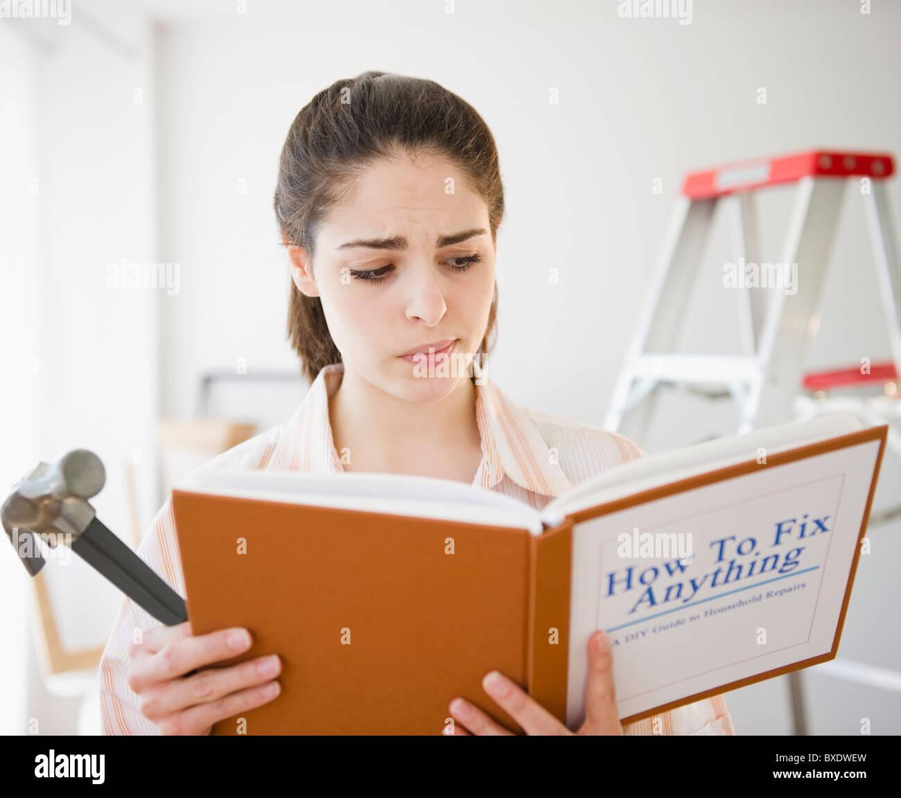 Verwirrt Frau liest, tun Sie es selber buchen Stockbild