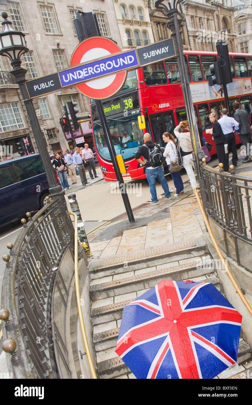 Piccadilly Circus Tube Ausfahrt mit einer Frau zu Fuß die Treppe mit einem Union Jack-Schirm Stockbild