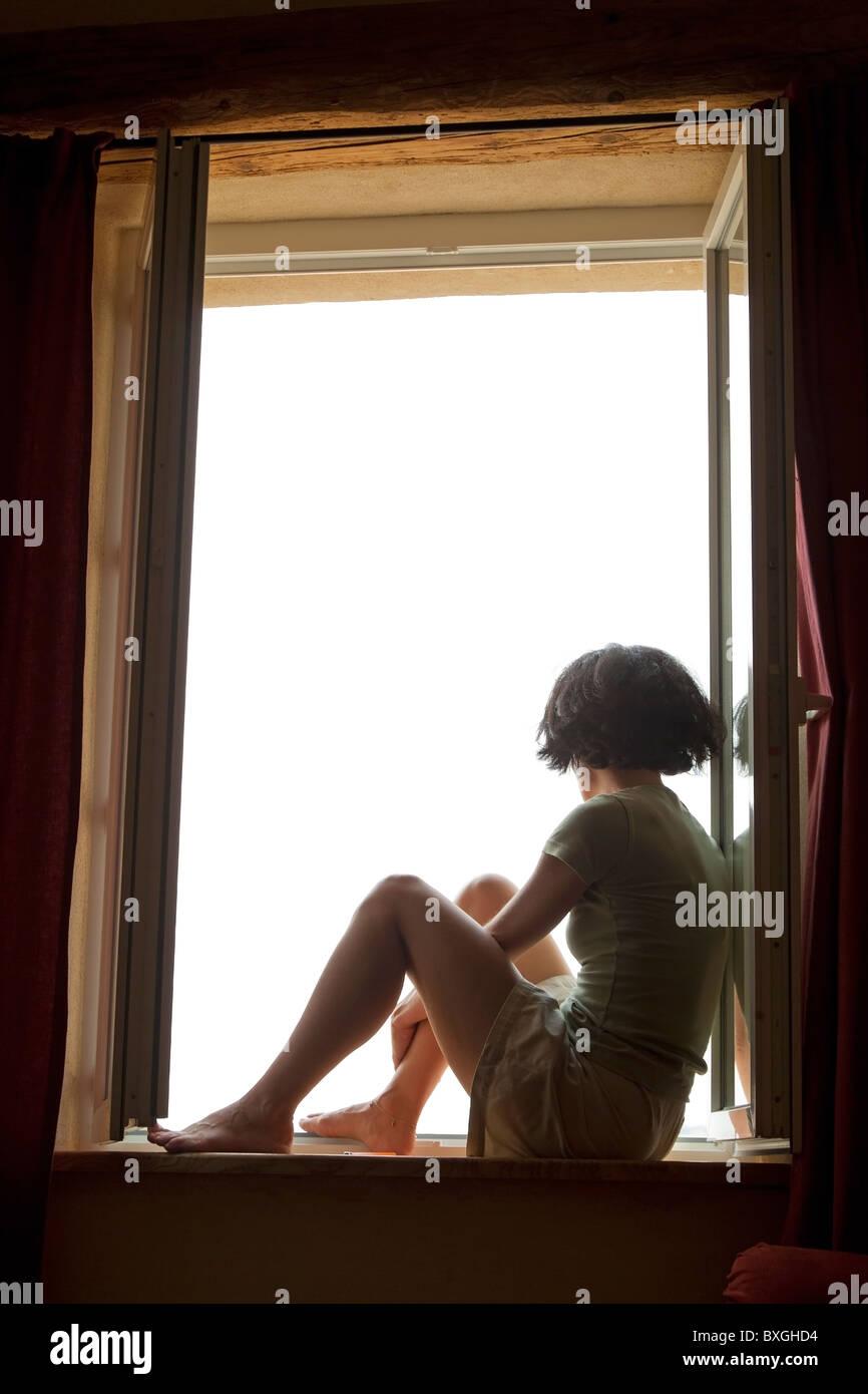 Frau aus dem Fenster schauen Stockfoto