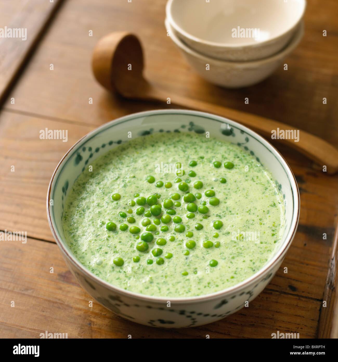 Gekühlte Salat Suppe in eine Schüssel mit Erbsen an der Spitze Stockbild