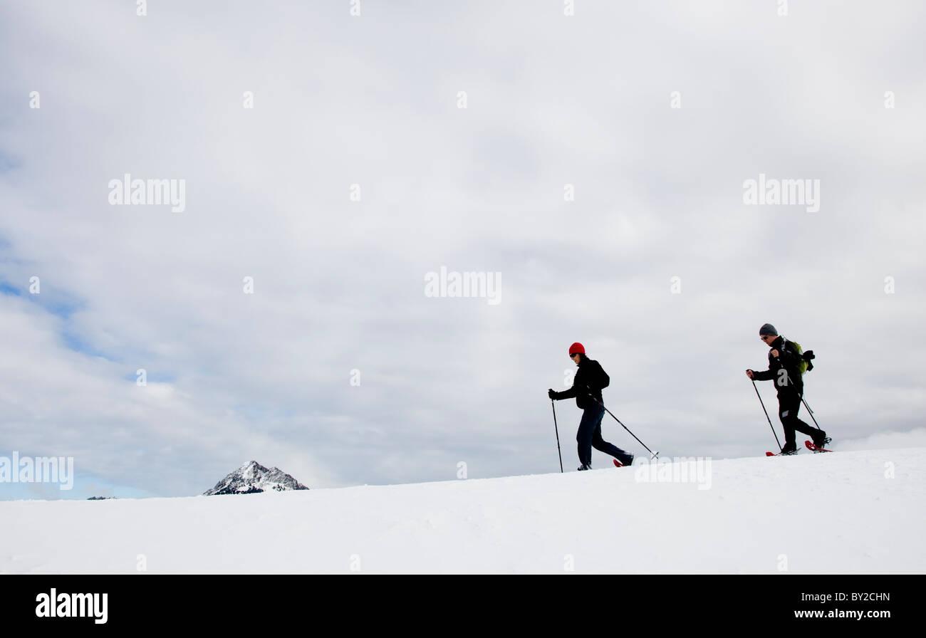 Zwei Menschen, Schneeschuhwanderung entlang einer Kante an einem bewölkten Tag. Stockbild