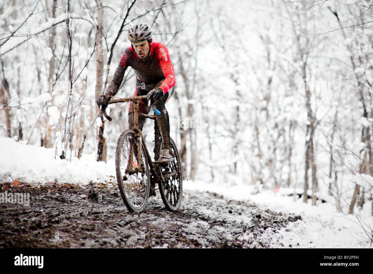 Ein Radfahrer Rennen im Schlamm und Schnee an einem Cyclocross-Rennen in Boulder, Colorado. Stockbild