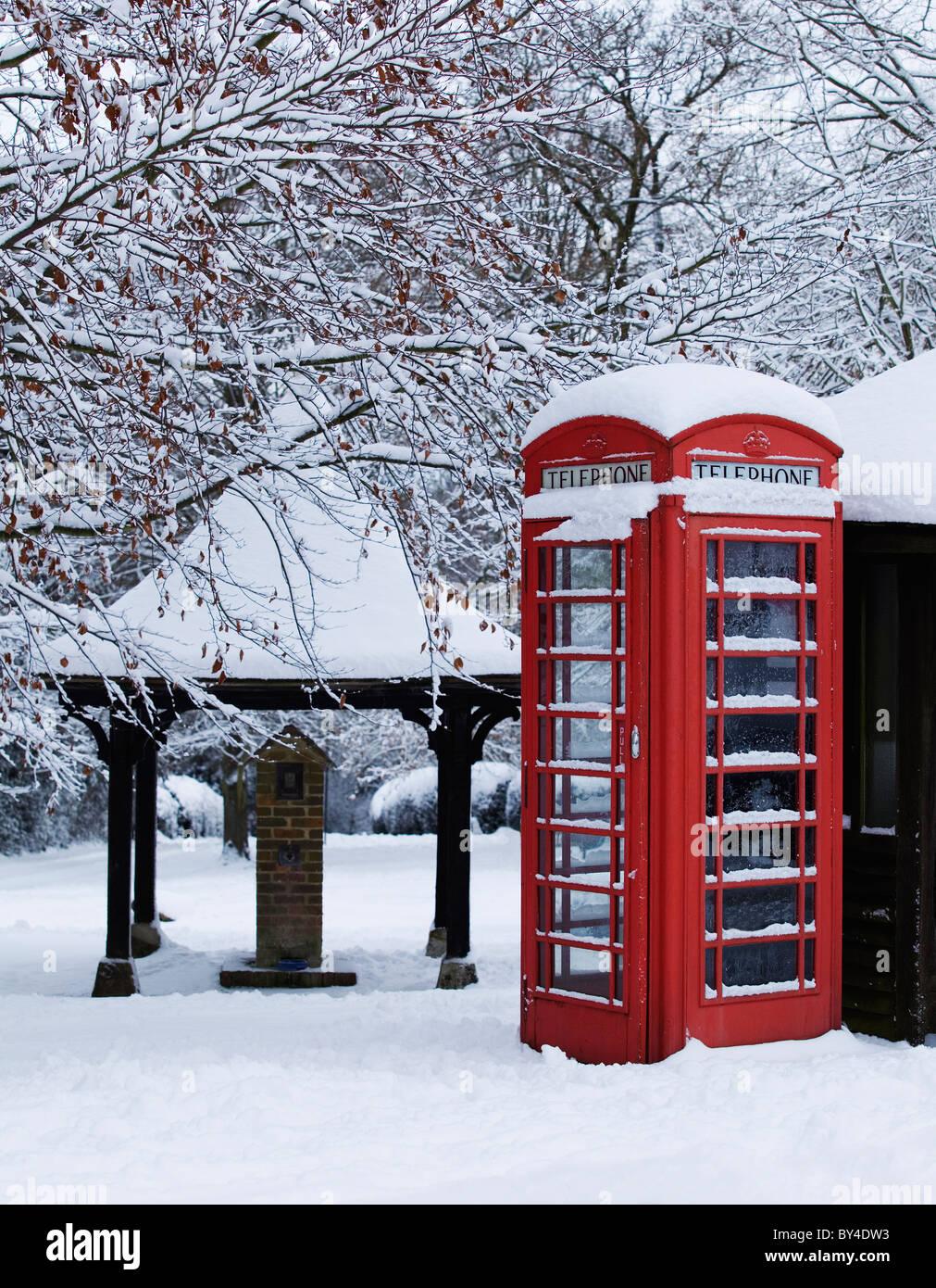 Traditionelle rote Telefonzelle mit Schnee auf einem englischen Dorfgrün Stockbild