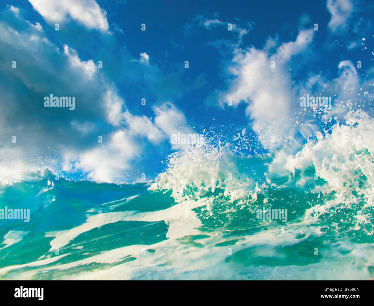 Green Wave mit blauen Wolkenhimmel hinter dem zusammenstoßen. Foto aufgenommen am La Canteras Strand, Gran Stockbild