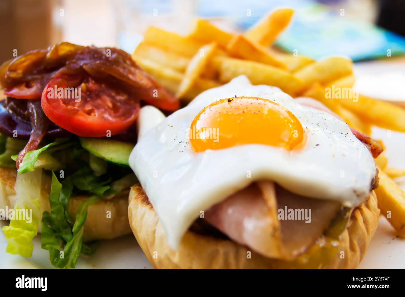 Wagyu-Beef-Burger mit Chips, Speck, Schinken, Ei und Gemüse Stockbild