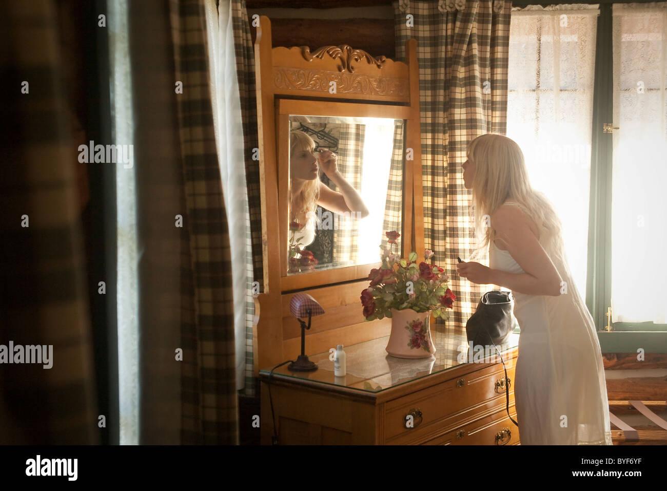 Frau macht im Spiegel Stockbild