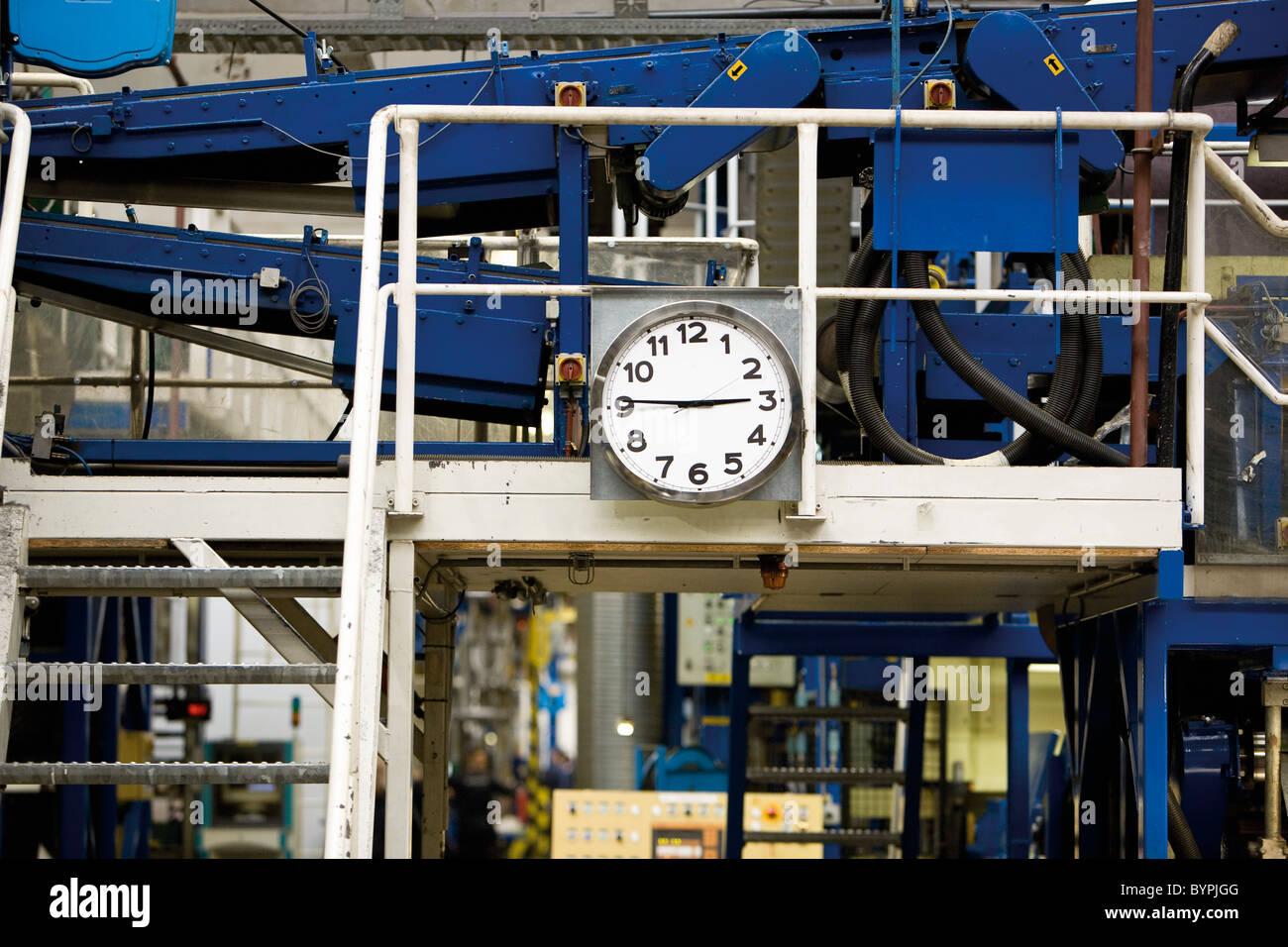 Uhr montiert neben Metall-Treppe im Teppich Fliesenwerk Stockbild