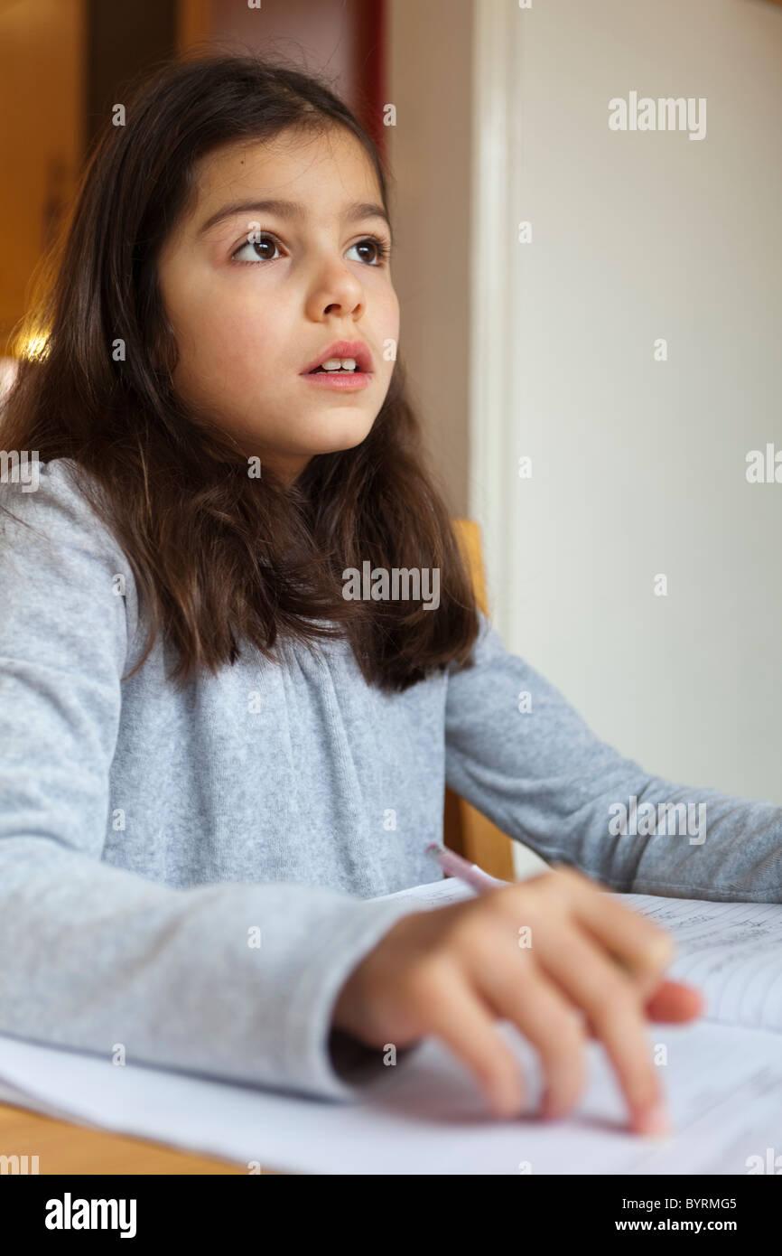 8 Jahre altes Mädchen, die ihre Hausaufgaben Stockbild