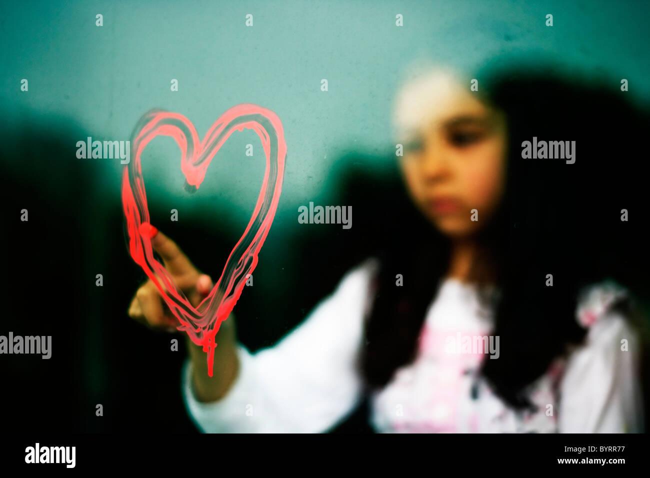 Mädchen zieht Herzform auf schmutzige Fenster mit ihrem Finger in roter Farbe Stockbild
