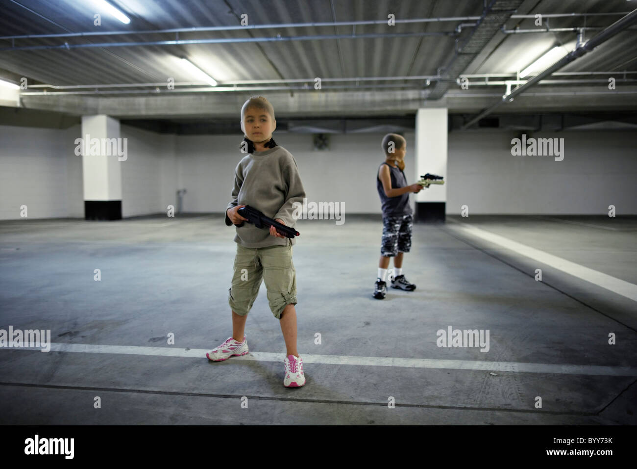 Kinder mit Strumpf Masken und Spielzeugwaffen in Tiefgarage vorzubereiten für große Bankraub. Stockbild