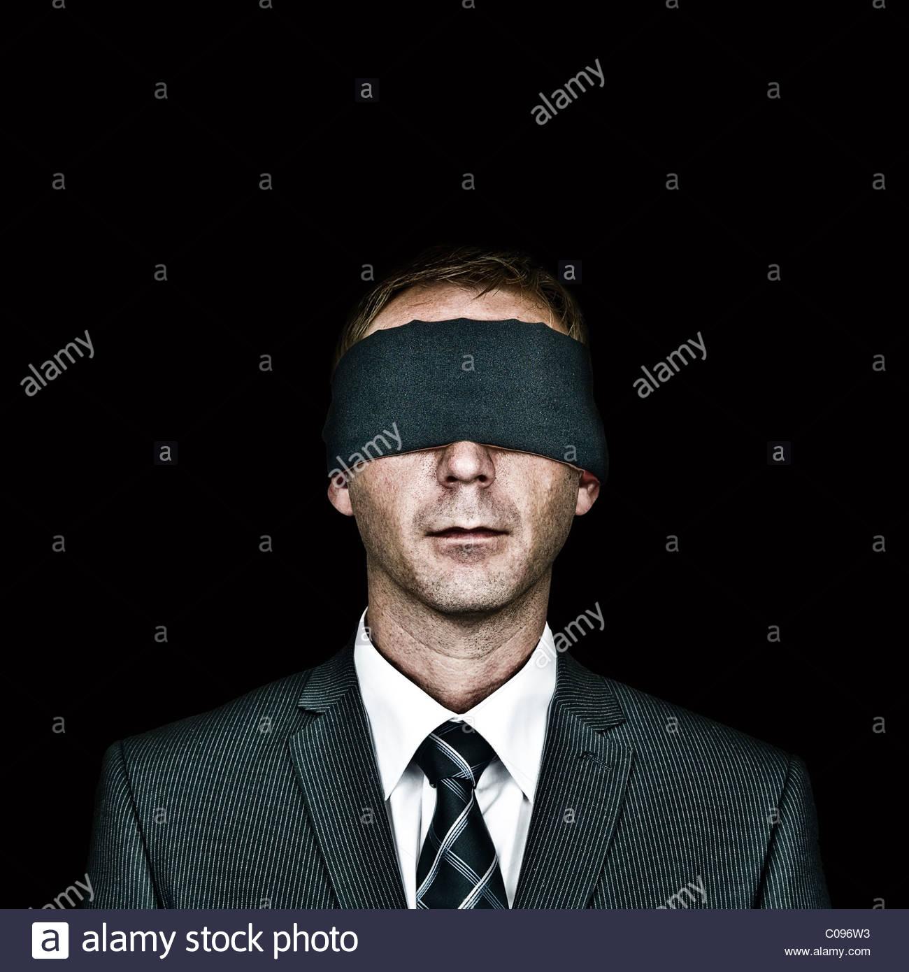 Mann mit verbundenen Augen auf schwarzem Hintergrund Stockbild