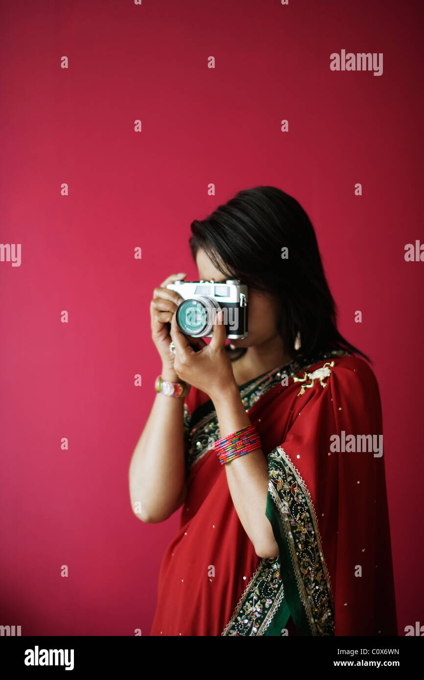 Punjabi Frau im roten Sari nimmt Bild mit alten Film-Kamera Stockbild