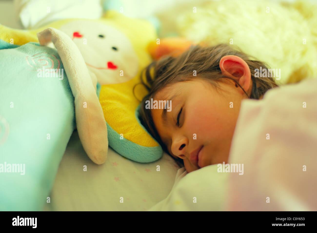 Mädchen hat Lüge mit Spielzeugpuppe im Bett. Stockbild