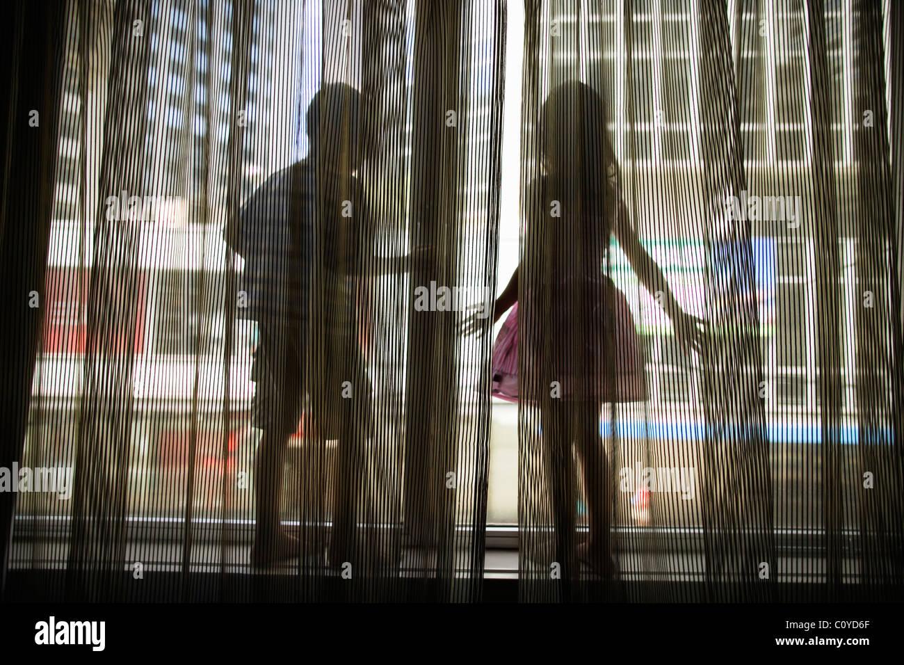 Jungen und Mädchen stehen auf der Fensterbank mit Blick auf Stadt, Wellington, Neuseeland Stockbild