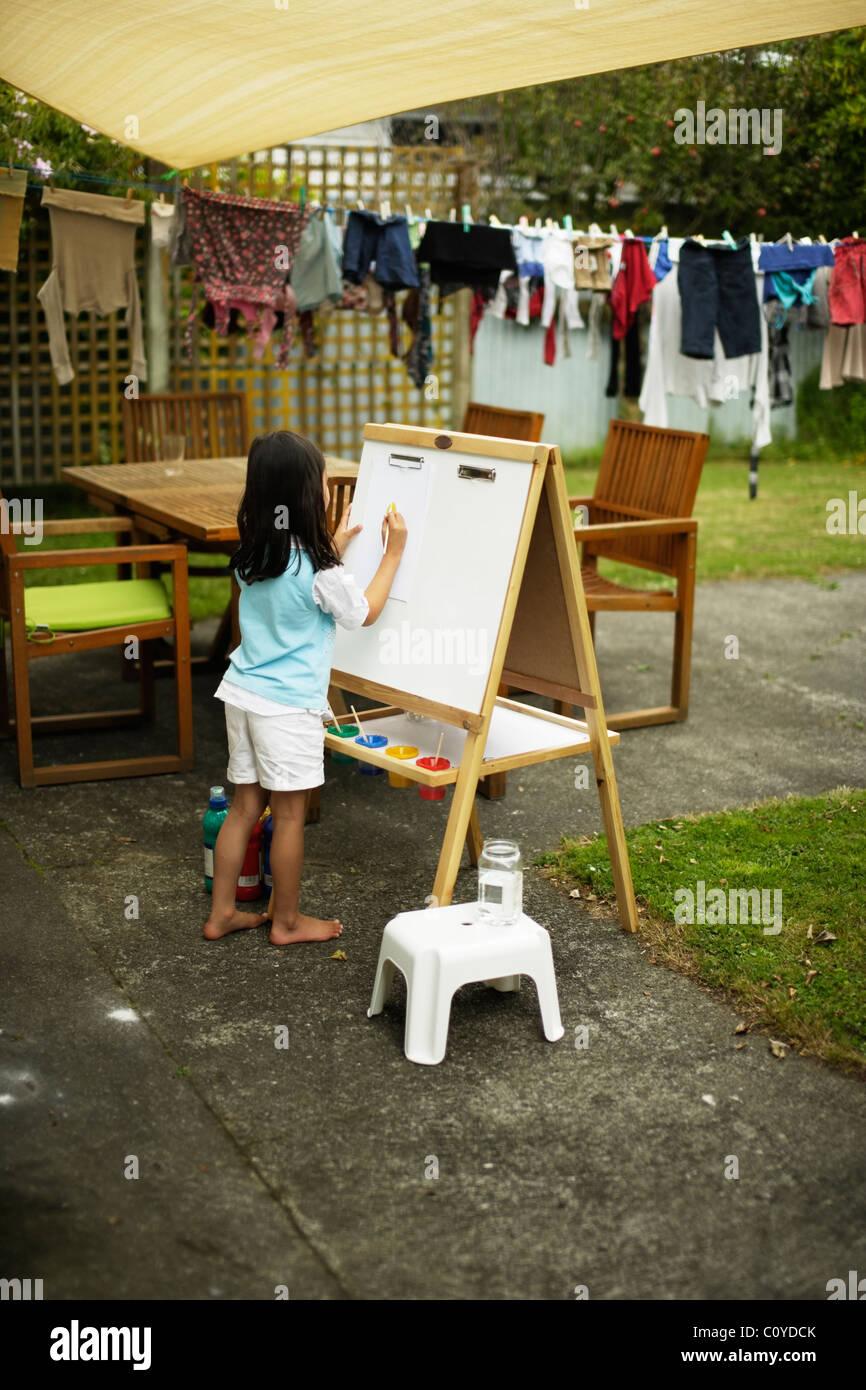 Mädchen malen an der Staffelei im Hinterhof. Stockbild